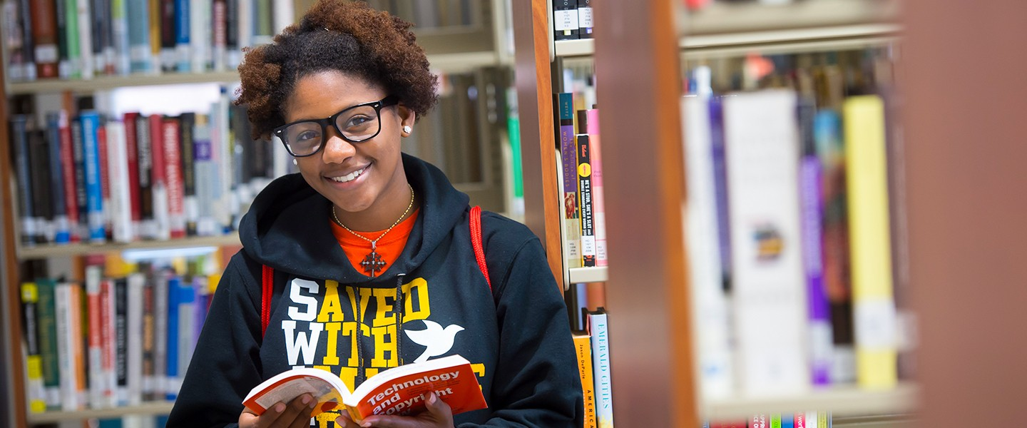 A student looking through books in the McMillen library